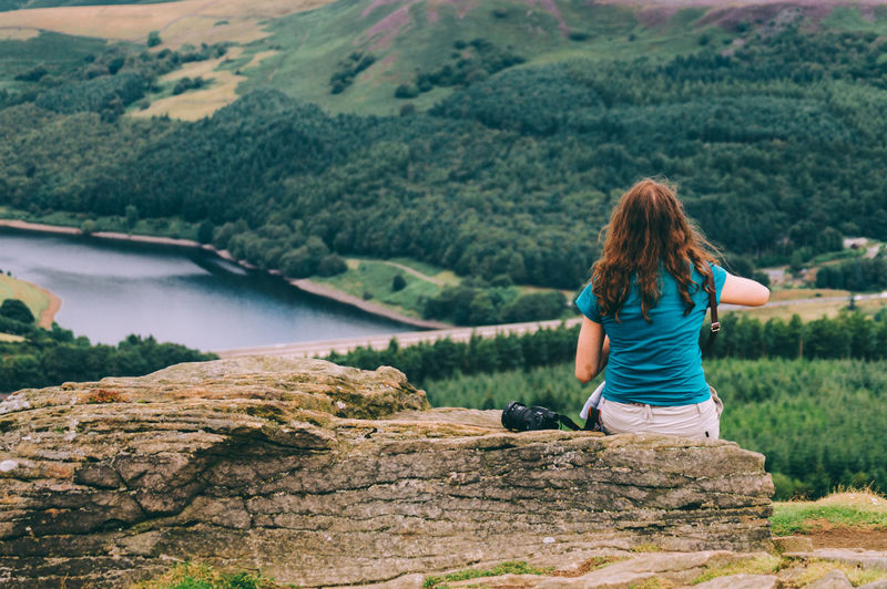 Rear view of woman sitting on rock by lake