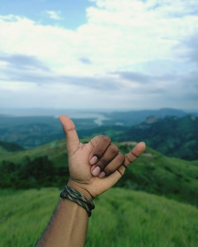 Cropped hand gesturing shaka sign against landscape