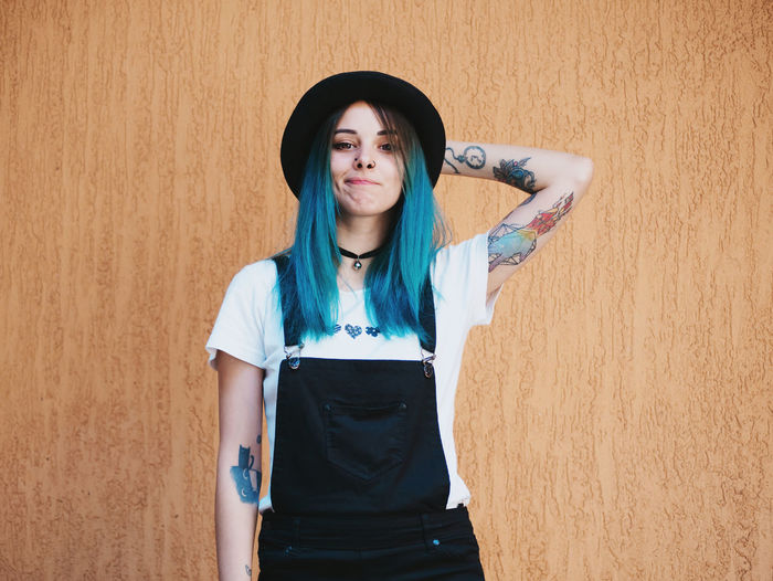 Portrait of hipster standing against wall