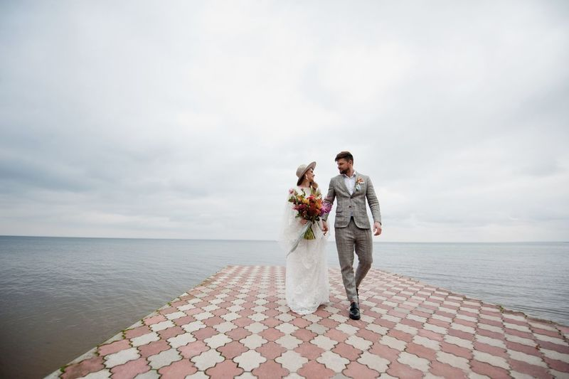 Newlywed couple walking on pier over lake against cloudy sky