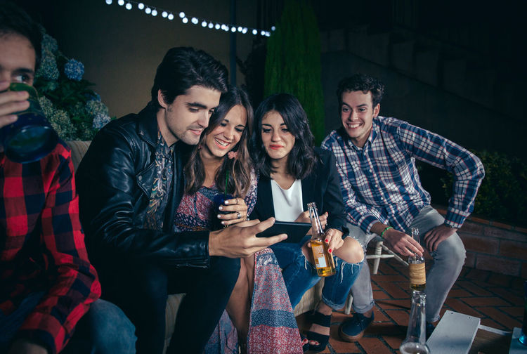 Group of happy young friends drinking and laughing while looking a smartphone picture in a outdoors party. Friendship and celebrations concept. Celebration Friends Fun Happiness Happy Horizontal Young Alcohol Cheerful Drink Entertainment Friendship Group Group Of People Looking Night Nightlife Outdoors Party People Phone Photo Smartphone Smiling Sofa