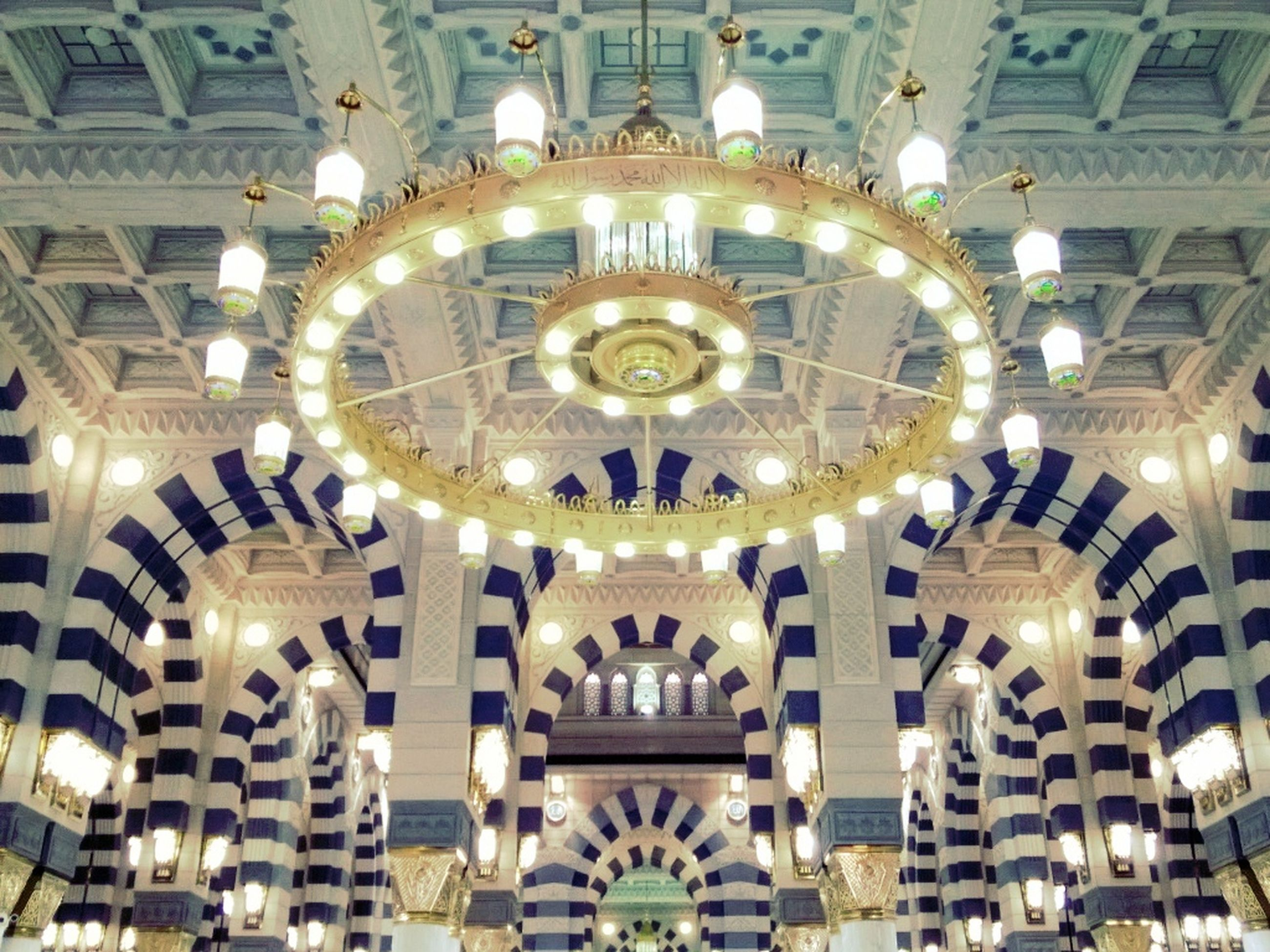 indoors, ceiling, architecture, built structure, low angle view, illuminated, place of worship, religion, ornate, church, chandelier, arch, hanging, circle, spirituality, design, lighting equipment, dome, famous place