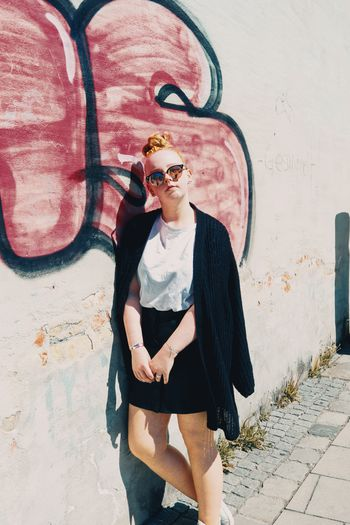 Portrait of woman wearing sunglasses while leaning on wall