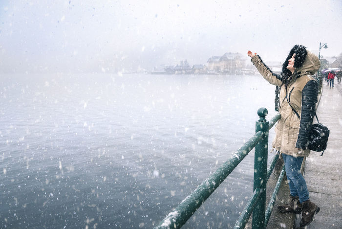 Happy young woman enjoying the first snowfall, reaching to catch snowflakes, on the Hallstatter See lakeshore, in the Hallstatt town, in Austria. Austrian Alps First Snow Winter Scenery Adult Cold Temperature Day Early Winter Full Length Hallstatt, Austria Hallstattersee Nature One Person One Young Woman Only Outdoors People Side View Sky Standing Warm Clothing Water Winter Women Young Adult Young Women