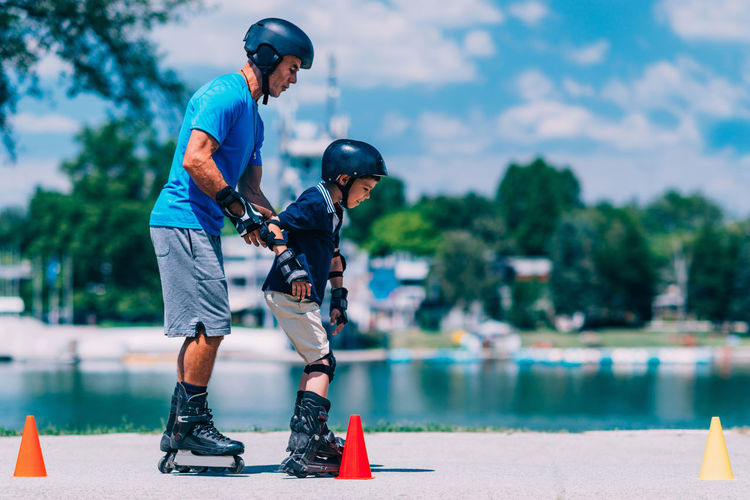 Grandfather holding grandson while rollerblading by lake
