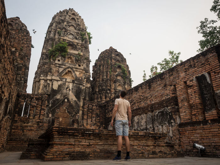 Rear view of a man standing in front of temple, sukhothai, thailand