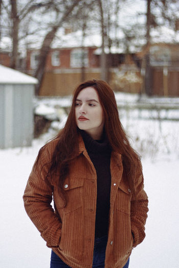 Young Woman Looking Away While Standing On Snow Covered Field