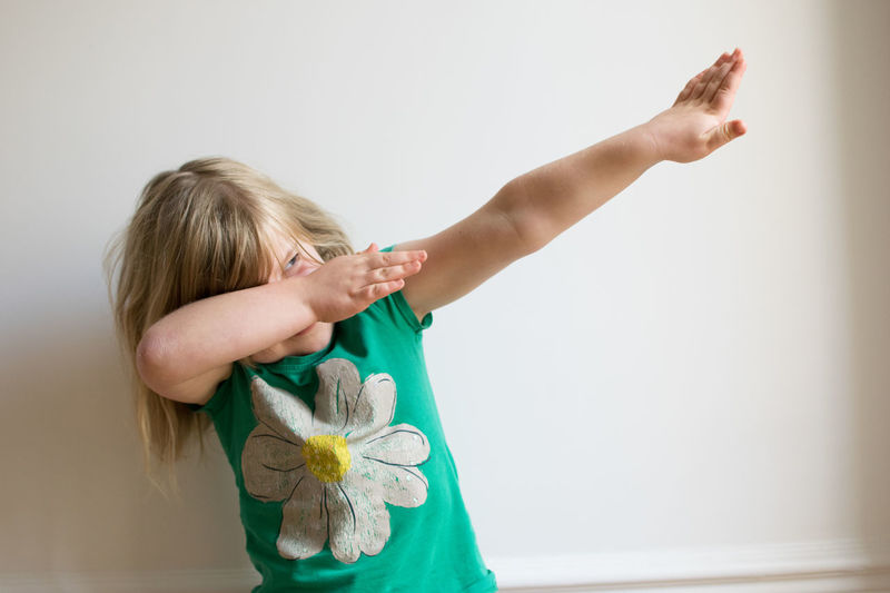 Mischievous girl in studio smiling Blue Eyes Bolt Fun Happy Studio Blond Hair Caucasian Childhood Day English Girl Girls Green Color Green T-shirt Human Hand Indoors  Lightening Bolt Mischievious Mischievous One Girl Only One Person People Standing Studio Shot White Background