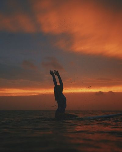 Silhouette young woman surfing on sea against cloudy sky during sunset