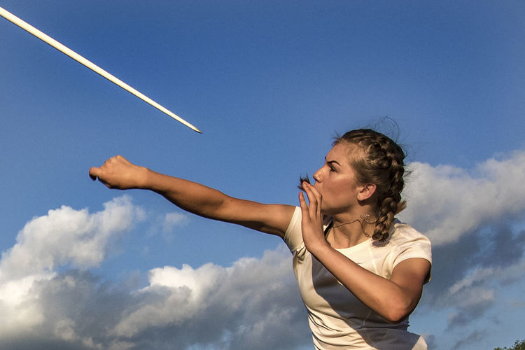 Low angle view of athlete throwing javelin against blue sky