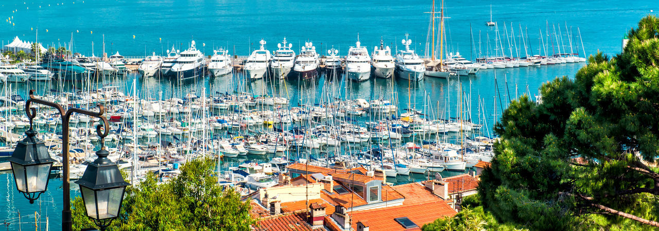 High angle view of sailboats moored in sea against buildings in city