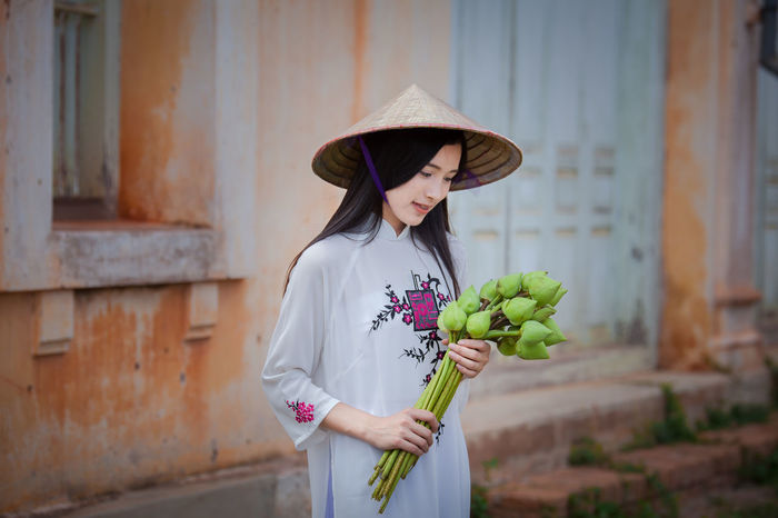 Woman dressed Vietnamese Vietnamese Architecture Beautiful Woman Building Exterior Built Structure Casual Clothing Day Dressed Focus On Foreground Hat Healthy Eating Holding Leisure Activity Lifestyles One Person Outdoors Portrait Real People Standing Young Adult Young Women