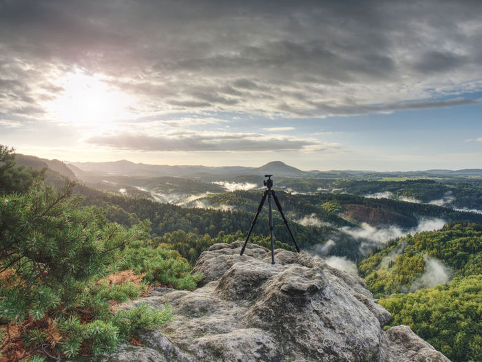 Tripod on peak ready for photography. sharp autumn rocky peaks with hills and mist in deep valley