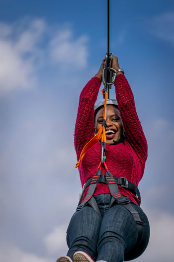 Low angle view of woman holding rope against sky