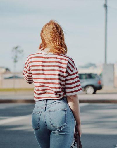 Rear View Of Woman Walking On Road