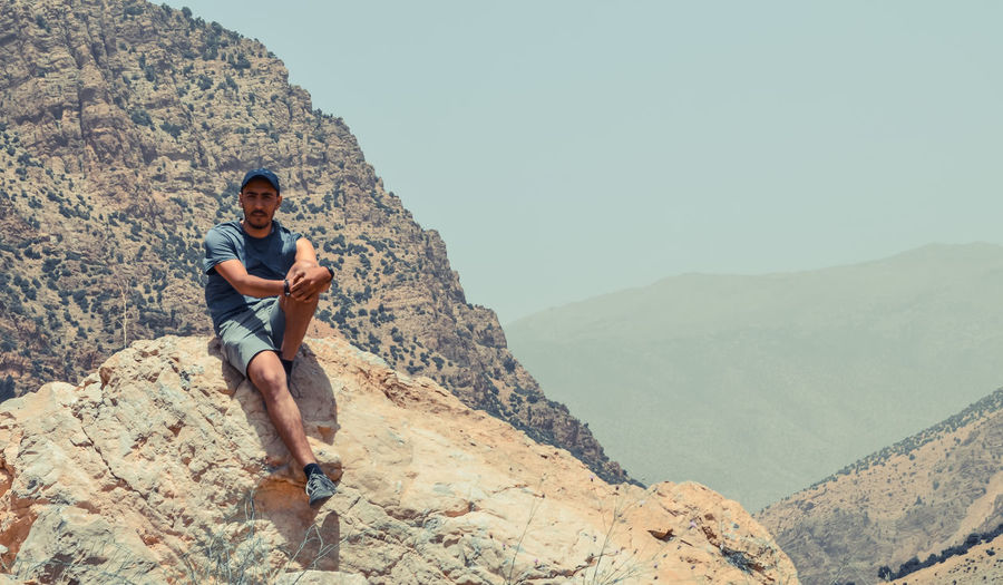 Young man sitting on rock against mountains