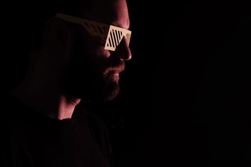 Close-up of man in 3-d glasses against black background