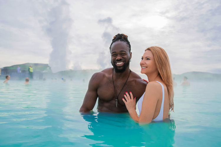 Happy couple standing in hot spring