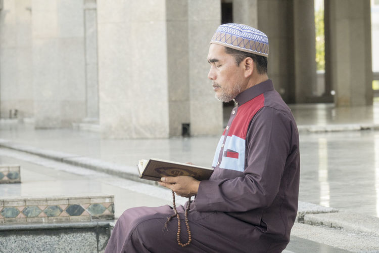 Mature Man Reading Koran While Sitting At Mosque