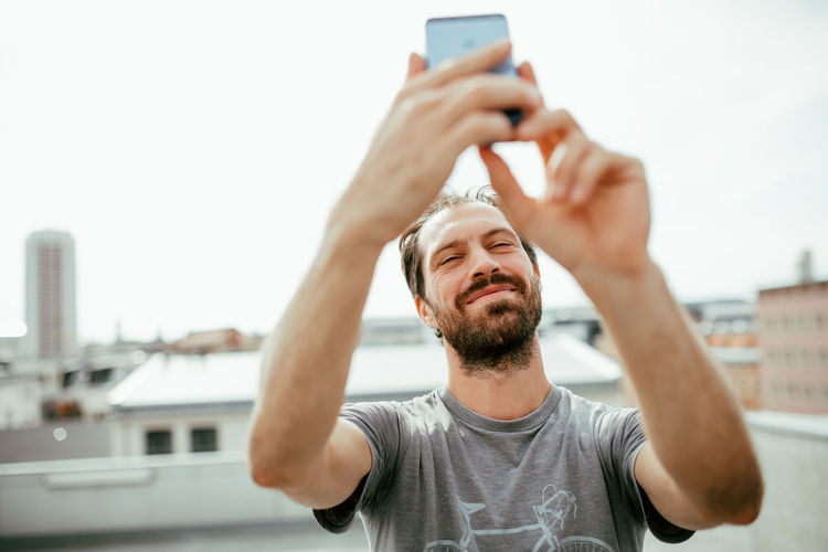 Smiling mid adult man taking selfie with smart phone in city
