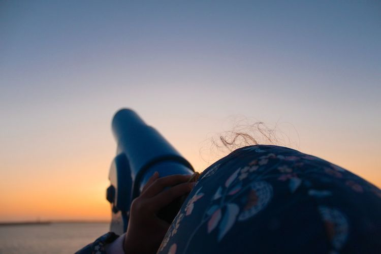 Close-up of woman looking through telescope against sky during sunset