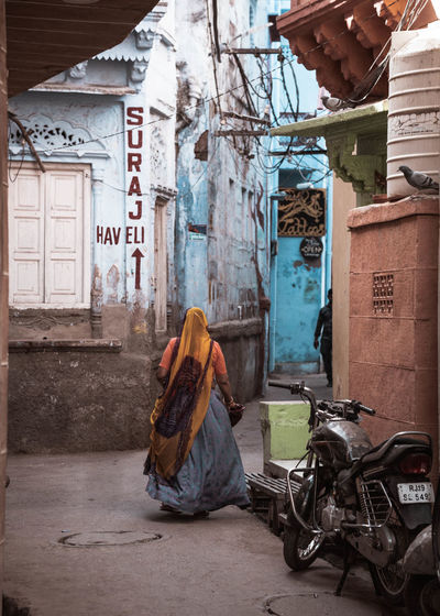 Rear view of woman sitting on street against buildings in city