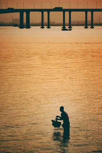 Silhouette man standing in sea during sunset