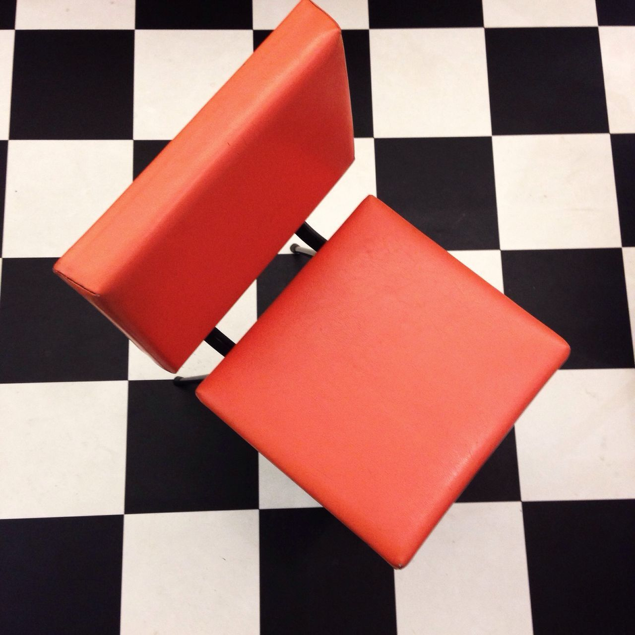 High angle view of orange chair on checkered floor