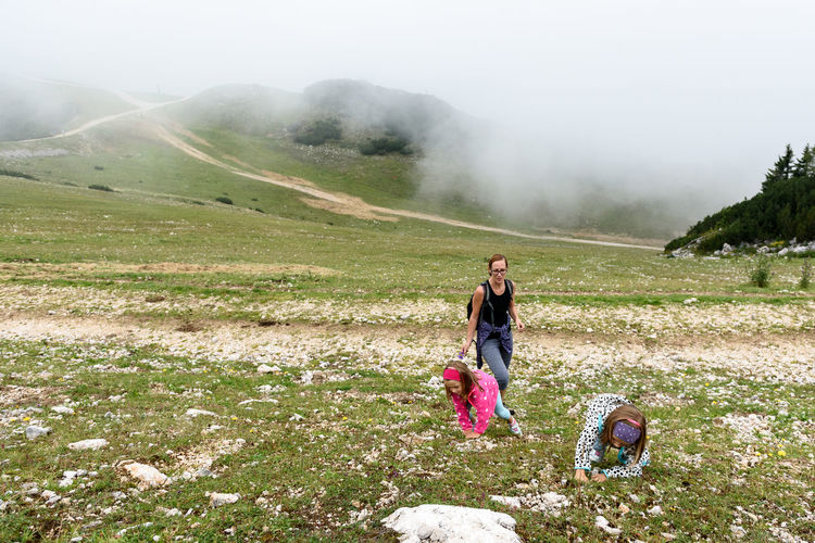 Mother and daughters hiking on mountain in foggy weather