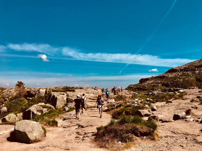 People walking on rock landscape against sky