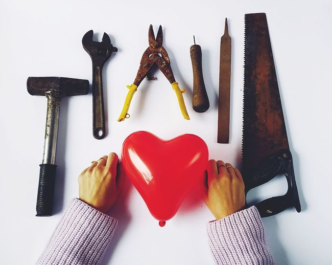 Cropped Hands Of Woman With Red Heart Shape Balloon And Work Tools Over White Background