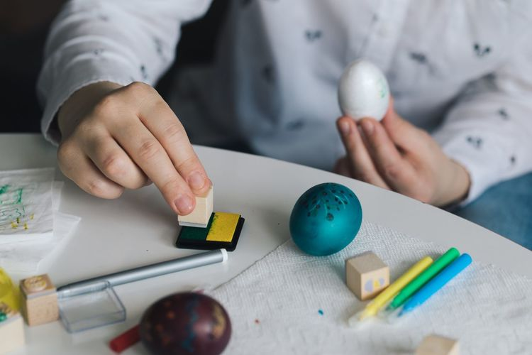 Midsection of woman decorating easter egg