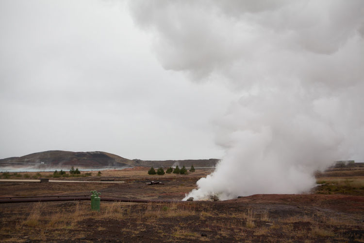 Smoke emitting from volcanic landscape against clear sky