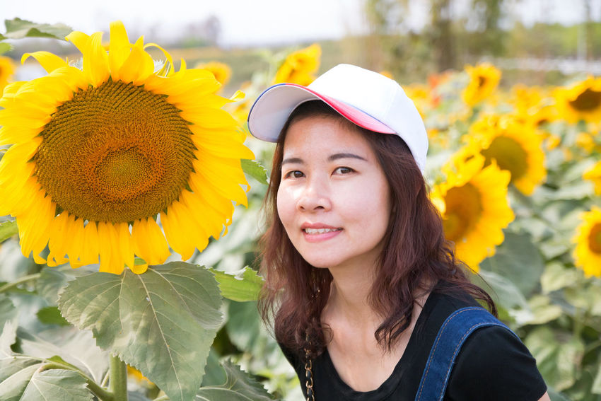 enjoy with sunflower Adult Adults Only Beautiful Woman Beauty Beauty In Nature Crown Flower Flower Head Happiness Headshot Human Face Knit Hat Knitted  Leaf Lifestyles Nature One Person Only Women Outdoors People Plant Portrait Smiling Women Young Adult