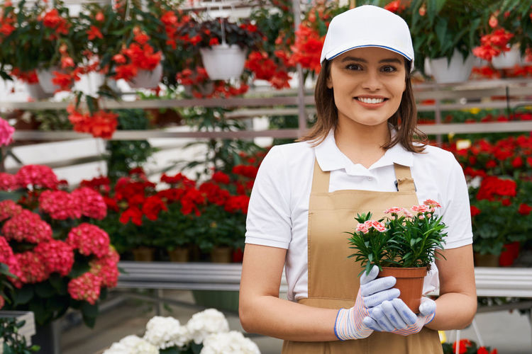 Portrait of young smiling florist holding flowering plants