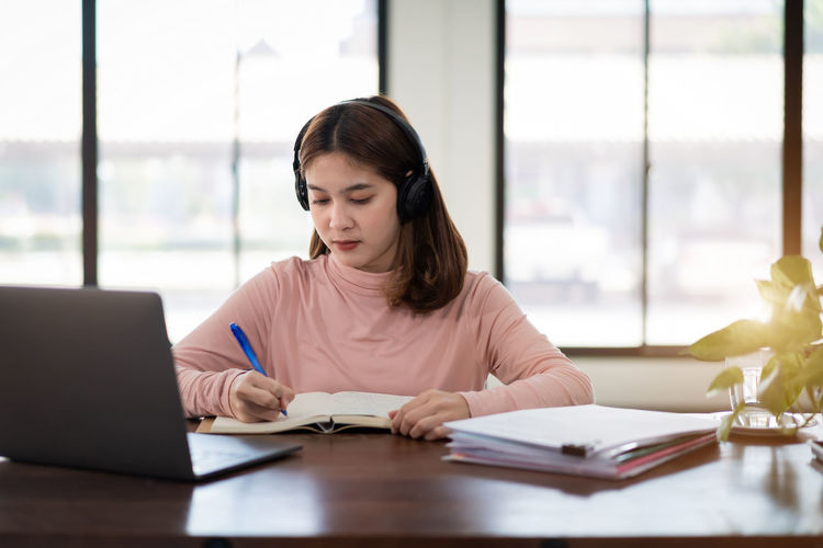 Young woman writing in book at classroom