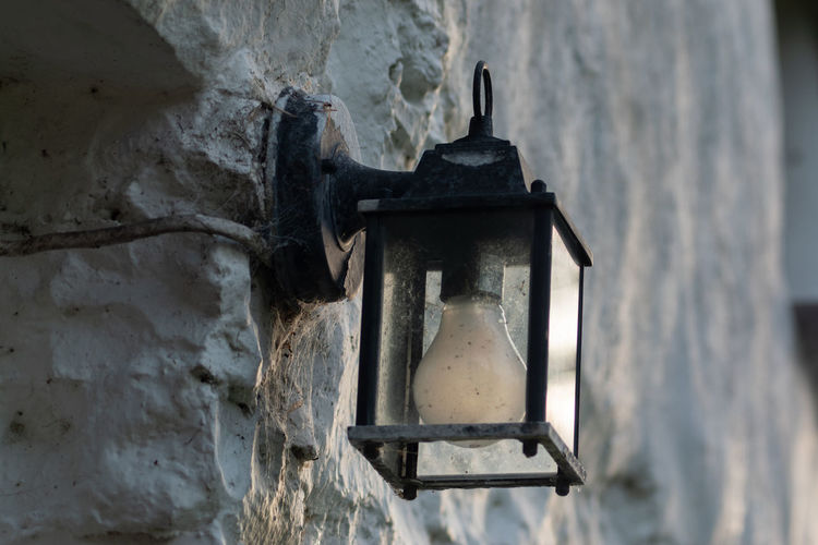 Close-up of old lamp hanging against wall