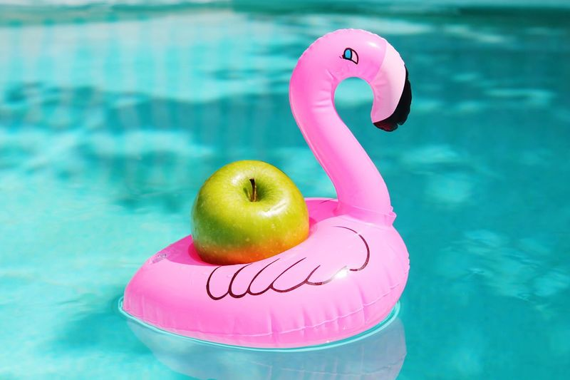 Apple In Inflatable Duck On Swimming Pool
