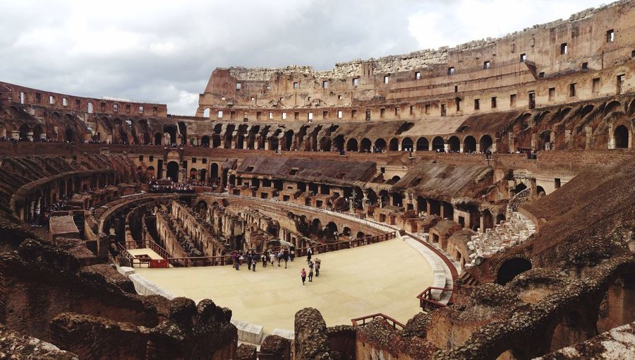 View of coliseum against cloudy sky