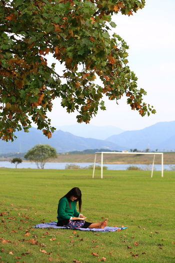 Man sitting on field by tree against sky