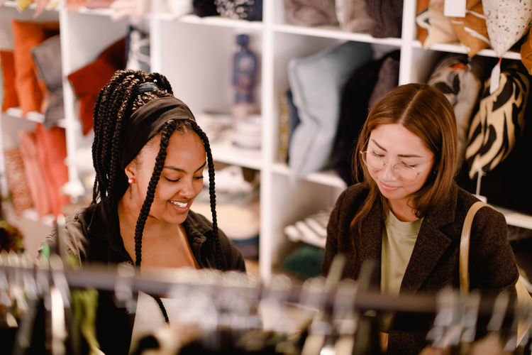 Smiling young woman looking away at store
