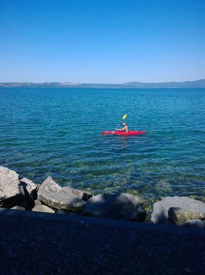 Man kayaking in sea against clear blue sky