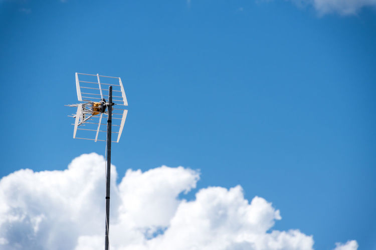 Low angle view of antenna against blue sky