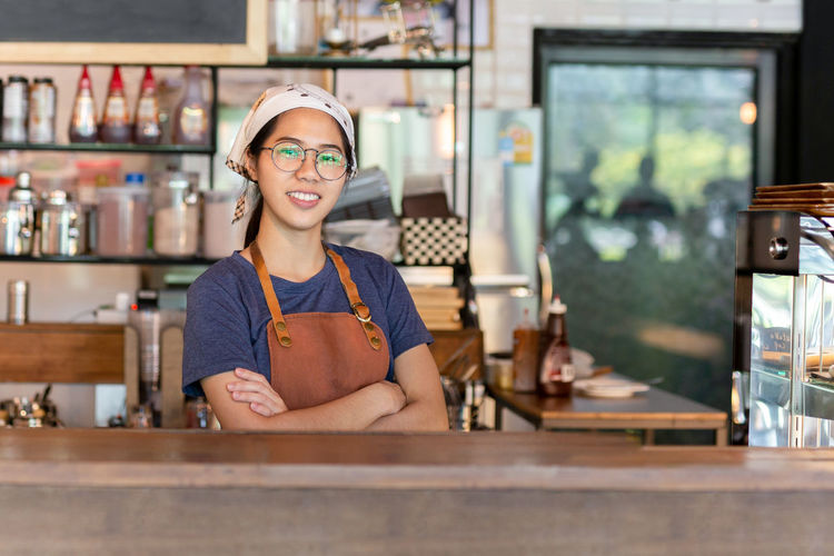Portrait of smiling waitress standing at cafe