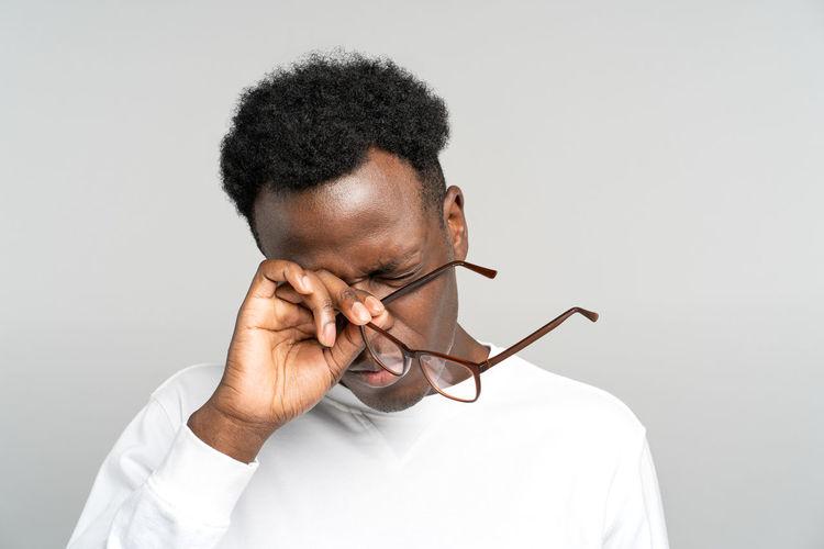 Portrait of man holding eyeglasses against white background