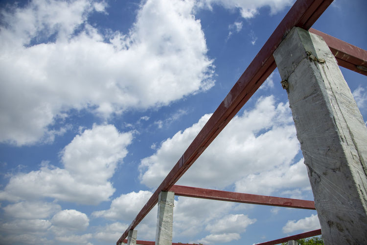 Low angle view of crane against cloudy sky