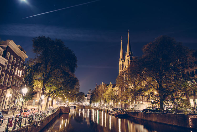 Canal in illuminated city by church against sky at night