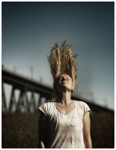 Young Woman Tossing Long Blond Hair Against Sky