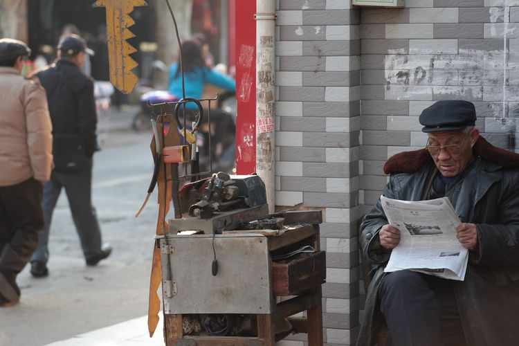 An old man with a key Real People Reading Time 配钥匙的老人 EyeEm China Street Life Streetphotography Key Of Life Real People Men City People Group Of People Architecture Street Walking