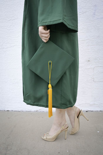 Low Section Of Woman Holding Mortarboard While Standing On Footpath